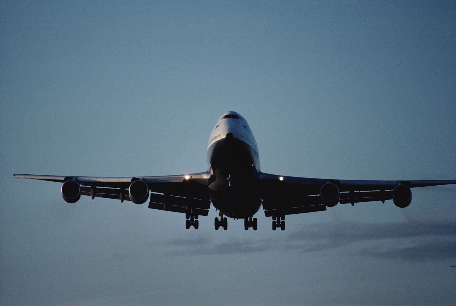 plane flying with landing gear down and lights on